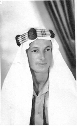 Portrait, wearing traditional Arab headress (keffiyah) and army shirt, [studio photograph, curtain drape in background] (kindly provided by family) - This image may be subject to copyright