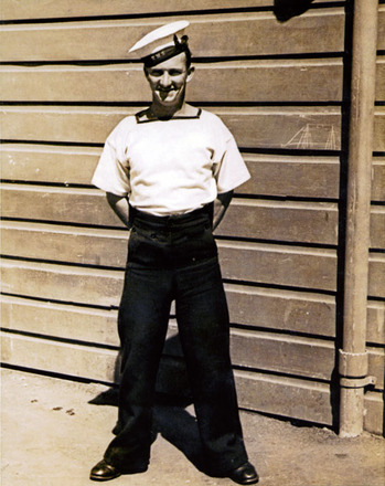 Portrait, WW2, Gilbert Hogan standing at ease in front of wooden buidling (kindly provided by his daughter Lynn) - This image may be subject to copyright