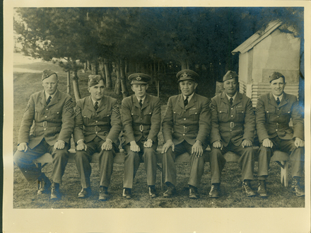 Group, WW2, 6 Airmen, 2 officers and 4 sergeants,seated on a bench near pine trees. Vernon Butler 3rd from left - This image may be subject to copyright