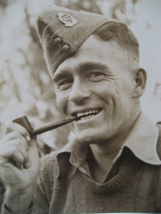 Portrait, WW2, wearing cap with badge, [hand]knitted jumper and pipe, Jack Callaghan (kindly provided by family) - This image may be subject to copyright
