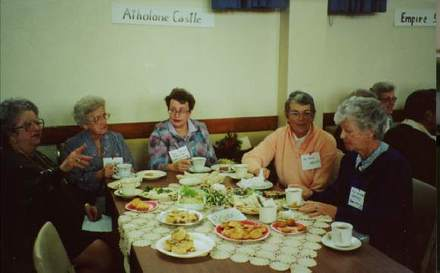 Reunion, war brides, Mt Eden War Memorial Hall, Auckland ca. mid 1990s, 5 women seated at a table with Athalane (sic) [Athlone] Castle sign. Left to right: unknown, unknown, ?Eileen Beresford wife of Keith Beresford (RNZAF), Val Wood, unknown. - This image may be subject to copyright