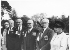 Group, 4 veterans and three women standing, large trees in background :Herbert Everett (4th from right) men in group wearing medals and [name] tag pinned to right side of jackets. [no date] Auckland War Memorial Museum - Tāmaki Paenga Hira PH-2005-37 - No known copyright restrictions
