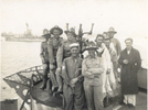 Group soldiers and sailors standing on the bow of a ship, Alexandria Harbour, 1941. Morris is at front with arms folded. Warship in the background. (photo kindly provided by family) - This image may be subject to copyright