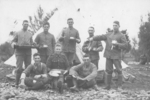 Group, soldiers with eating utensils, arranged for the photograph outside tent, foreground very rocky, seated soldier boots with hobnails, soldier pretending to tip liquid from cup onto another soldier seated, tin cups, plates, knife, metal roasting dish, Fred Baker standing back left holding metal roasting dish, other soldiers unknown. - No known copyright restrictions