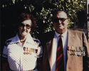 Portrait, Mr Hubert Crispin & Mrs Mary Crispin nee (Stapleton) standing outside in front of a tree, in later life, wearing medals. Annotated at back early 1980's at 36 Owen's Road, Epsom, Auckland - This image may be subject to copyright
