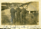"""Group, WW2, three soldiers standing between corrugated iron barracks, washing hanging out of windows annotated """" Sid & two of his mates at Trentham"""" - This image may be subject to copyright"""