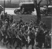 Group, soldiers marching in a street, Norman (middle front row) on parade in Christchurch prior to leaving for Egypt in August 1940 - This image may be subject to copyright