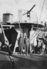 Group, 2 soldiers, 28 Maori Battalion, Aquitania 1940, Alex Leger (26514) with great coat and hat (left) and Vailima (26147) (right), hat, hands in pockets standing in front of gun turrets aboard ship 1940 - This image may be subject to copyright
