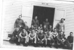 Group photo [WW2 ?], soldiers informally photographed outside, in front of a wooden shed numbered 16 - This image may be subject to copyright