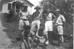 Group 5 soldiers and 1 Fijian woman, Fiji, in front of house, Ian in shorts. - This image may be subject to copyright