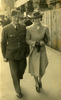 Airman, Morrison in uniform walking along a street [near central PO, Auckland?] with Alice wearing coat, gloves, hand bag tucked under her arm. - This image may be subject to copyright