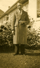 Portrait Leslie Gordon Jackson (66110) standing in civilian clothes, wearing a thick long overcoat in a garden, plants, house windows behind. - This image may be subject to copyright