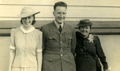 Family group, left to right Alice Morrison in a striped buttoned frock with white collar, short sleeved white cuff, hat, Morrison in uniform and a friend wearing a dark frock, . - This image may be subject to copyright