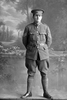 Full length portrait of Sergeant Ashton, probably Sergeant Norman Ashton, Reg No 24323, of the 17th Reinforcements, Auckland Infantry Regiment, J Company, (Corporal in the Roll of Honour), killed in action in France on 4 October 1917, at the Battle of Passchendaele. (Photographer: Herman Schmidt, 1916). Sir George Grey Special Collections, Auckland Libraries, 31-A1811. No known copyright.