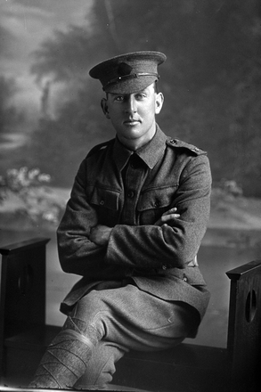 Full portrait of Rifleman Claude Roy Ayling seated. Reg No. 23/59, of the New Zealand Rifle Brigade. (Photographer: Herman Schmidt, 1915). Sir George Grey Special Collections, Auckland Libraries, 31-A1819. No known copyright.