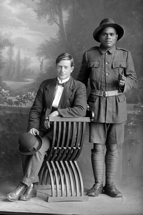 Full portrait of two men, Private Aki standing, Reg No 19232, Maori Contingent (11th Reinforcements - Rarotongans). New Zealand Maori Pioneer Battalion. (Photographer: Herman Schmidt, 1916). Sir George Grey Special Collections, Auckland Libraries, 31-A3315. No known copyright.