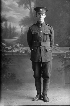 Full length portrait of Rifleman Lewis Arthur William Beecroft, Reg No 24/1594, of the New Zealand Rifle Brigade, 3rd Reinforcements to the 2nd Battalion, - F Company. (Photographer: Herman Schmidt, 1916). Sir George Grey Special Collections, Auckland Libraries, 31-B1444. No known copyright.