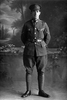 Full length portrait of Lance - Corporal Charles Basil Beeson Reg No 26535 of the 8th Reinforcements to the 4th Battalion - H Company, New Zealand Rifle Brigade. Killed in action in France 8 Sep 1918. (Photographer: Herman Schmidt, 1916). Sir George Grey Special Collections, Auckland Libraries, 31-B1853. No known copyright.
