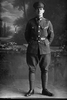 Full length portrait of Lance - Corporal Charles Basil Beeson Reg No 26535 of the 8th Reinforcements to the 4th Battalion - H Company, New Zealand Rifle Brigade. Killed in action in France 8 Sep 1918. (Photographer: Herman Schmidt, 1916). Sir George Grey Special Collections, Auckland Libraries, 31-B1854. No known copyright.