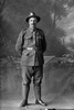 Full length portrait of Edwin George Bartlett, Reg No 40482, Auckland Infantry Regiment, - A Company, 23rd Reinforcements. (Photographer: Herman Schmidt, 1916). Sir George Grey Special Collections, Auckland Libraries, 31-B2379. No known copyright.
