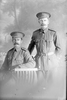 3/4 portrait of Sapper William Coldicutt, Reg No 4/1244 (standing), and Sapper Oswald Charles Cossey, Reg No 4/1251 (seated) both of the New Zealand Tunnelling Company (Photographer: Herman Schmidt, 1915). Sir George Grey Special Collections, Auckland Libraries, 31-C310. No known copyright.