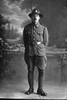 Full length portrait of Lance Corporal Henry Richard Cowan, Reg No. 23322, of the 7th Reinforcements to the 1st Battalion, - E Company, New Zealand Rifle Brigade (Photographer: Herman Schmidt, 1916). Sir George Grey Special Collections, Auckland Libraries, 31-C321. No known copyright.