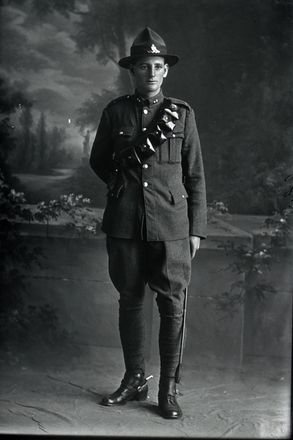 Full length portrait of Gunner John Edwards, Reg No 12762, of the New Zealand Field Artillery. (Photographer: Herman Schmidt, 1916). Sir George Grey Special Collections, Auckland Libraries, 31-E1981. No known copyright.