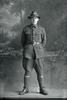 Full length portrait of Private T J McEldowney of the New Zealand Mounted Rifles, 11th Reinforcements (Photographer: Herman Schmidt, 1916). Sir George Grey Special Collections, Auckland Libraries, 31-E1983. No known copyright.