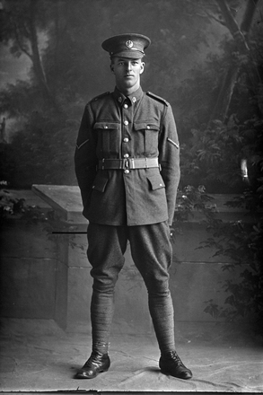 Full length portrait of Lance Corporal John William Gow, Reg No 11462, of the Auckland Infantry Battalion, - A Company, 12th Reinforcements. (Photographer: Herman Schmidt, 1916). Sir George Grey Special Collections, Auckland Libraries, 31-G495. No known copyright.