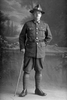 Full length portrait of Private Vivian Leonard Gittos, Reg No 3/2509, of the New Zealand Medical Corps wearing 4 years of Service Chevrons and campaign medals (Photographer: Herman Schmidt, ). Sir George Grey Special Collections, Auckland Libraries, 31-G4265. No known copyright.