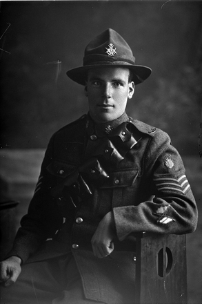 3/4 portrait of Sergeant Thomas Douglas Hutcheon, Reg No 4/329, of the New Zealand Engineers, Divisional Signallers, New Zealand Signal Corps, ex of the Samoan Advance Party. Wearing crossed flags trade badges of an instructor. Died of wounds in France on 17 August 1917 at the Battle of Ypres. (Photographer: Herman Schmidt, 1916). Sir George Grey Special Collections, Auckland Libraries, 31-H2004. No known copyright.