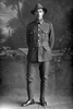 Full length portrait of Rifleman Gilbert John Neal, Reg No 24/249, of the New Zealand Rifle Brigade, - A Company. (Photographer: Herman Schmidt, 1915). Sir George Grey Special Collections, Auckland Libraries, 31-N871. No known copyright.