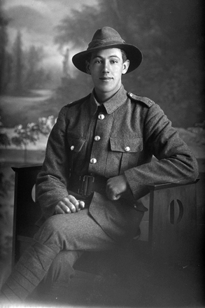 3/4 portrait of Rifleman Gilbert John Neal, Reg No 24/249, of the New Zealand Rifle Brigade, - A Company. (Photographer: Herman Schmidt, 1915). Sir George Grey Special Collections, Auckland Libraries, 31-N872. No known copyright.