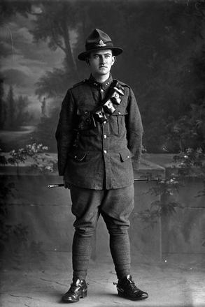 Full length portrait of Gunner Eric Gordon Sherson, Reg No 17229, of the New Zealand Field Artillery. (Photographer: Herman Schmidt, 1916). Sir George Grey Special Collections, Auckland Libraries, 31-S2151. No known copyright.