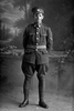 Full length portrait of Lance Corporal (Corporal in the nominal roll) Albert Victor Tyer, Reg No 12/3174, of the 3rd (Auckland) Regiment, Auckland Infantry Regiment, 7th Reinforcements. (Photographer: Herman Schmidt, 1915). Sir George Grey Special Collections, Auckland Libraries, 31-T2175. No known copyright.