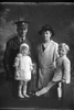 3/4 group portrait of 2nd Lieutenant Ralph William Warren, Reg No 18437, of the New Zealand Rifle Brigade, 8th Reinforcements to the 4th Battalion, - H Company, and his wife Mabel E Warren, and children, Tresca (left, then two years old) and Desmond (right, then four years old).  Lieutenant Warren was later with the Machine Gun Corps, he died of disease in the UK on 26 November 1918. (Photographer: Herman Schmidt, 1916). Sir George Grey Special Collections, Auckland Libraries, 31-W1277. No known copyright.