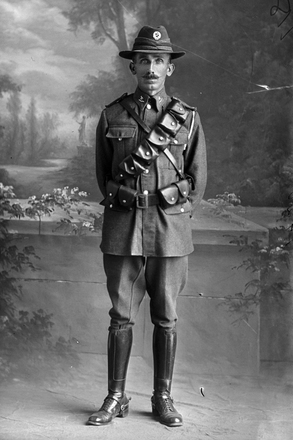 Full length portrait of Trooper Walter Workman, Reg No 13/2968, of the Auckland Mounted Rifles, - A Squadron, New Zealand Mounted Rifles. (Photographer: Herman Schmidt, 1916). Sir George Grey Special Collections, Auckland Libraries, 31-W1420. No known copyright.