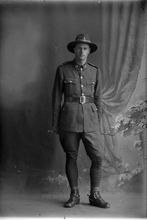 Full length portrait of Trooper Henry Fenton Waugh, Reg No 71830, of the New Zealand Mounted Rifles, 37th Reinforcements. (Photographer: Herman Schmidt, 1917). Sir George Grey Special Collections, Auckland Libraries, 31-W3967. No known copyright.