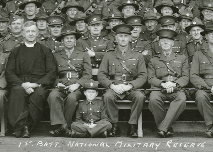 1st Battalion. National Military Reserve, 1941. Auckland, N.Z. Panoramic group portrait. Sir Gilbert Archey centre front row (detail). Auckland War Memorial Museum - Tamaki Paenga Hira. Image has no known copyright restrictions.