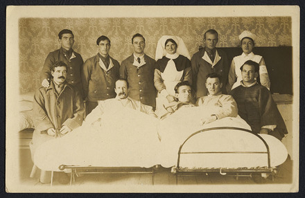 """Unknown photographer (1917) What do you think of our happy family?. Group portrait of patients, nurses and orderlies on a ward. Three male patients are posed in two hospital beds, each bed has additional male patients sitting either side. Standing behind are two nurses and four male staff. Inscription on verso reads: """"What do you think of our happy family? Room 12, Ward 2, Oatlands Park, Feb. 18th, 1917. Back Row - Mick Galoion, M.G.C; Lake Falconer, Ruskins boy, Charlie Coombes, 16th Waikato; Sister Miller; Burgess; Nurse Wilson. Front Row - Cpt. R. Colhoun, Tunnellers; H. Yates, 3rd Akd; Reeves Currie, 3rd 7. Arb(?); Sgt. Paddy Connell, Wgtn West Coast Ed Stern, Dio ...llers (?)."""" [sic]. Auckland War Memorial Museum call no. D570 M48 W241 p16. Image has no known copyright restrictions."""