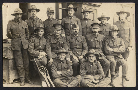 Unknown photographer (ca. 1916). Group portrait of 14 servicemen in uniform. Standing, left to right: possibly Thomas Holloway 12/754, John Leonard Bellerby 4/533, Alexander George McDonald 13/104, Edward Ralph Drake 13/180, Francis William Huia Mason 12/803, William Joseph Stancombe 12/133, Charles Gordon Nicol 13/112. Middle row, left to right: LM Bennett?, Chaplain Patrick Dore 13/655, Edwin Harrowell 12/907, John Macintosh Roberts 13/182. Seated, left to right: Aubrey Chitham Ollard 13/69A, Leonard Brookes 12/40A. Auckland War Memorial Museum call D501 P853 p1. Image has no known copyright restrictions.