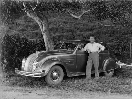 "Collins, Tudor Washington (photographer). Portrait of Tudor Collins standing next to a Chrysler automobile. ""X34.991"" is the number plate of the vehicle. Rugs, or blankets, are on the grass in the background. Plants, a tree, a post and wire fence, a grass hill, are also in the background. Auckland War Memorial Museum - Tāmaki Paenga Hira. Tudor Collins Collection PH-2013-7-TC-B824-16."