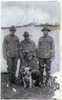 Photograph of Rifleman Thomas Samuel Tooman (s/n 26/918), with Caesar, the mascot of A Company, 4th Battalion, N.Z.R.B. Caesar's handler, standing on left and Caesar, being held by Private Albert Edward Griffin (s/n 3/1513). The other men are unidentified. Image kindly provided by Patricia Stroud. Image may be subject to copyright restrictions.