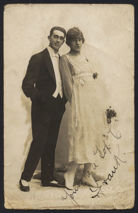 Heinrich, M. (ca. 1915) Frank Perkins (left) and female impersonator Stanley Lawson. Portrait of Stanley Lawson (3/1172) and Frank Perkins posing for the New Zealand Concert Party for a German photographer in Mulheim an der Ruhr. Stanley Lawson is dressed as a female in a wig, dress and high heels. Auckland War Memorial Museum call no. D570 E8 M956. Image has no known copyright restrictions.