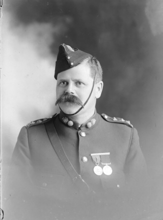 1/4 length portrait of Captain Percival Beaumont Greenhough 2/832. He is wearing the New Zealand Volunteer Service Medal and the Volunteer Long Service Medal. Sir George Grey Special Collections, Auckland Libraries, 31-68145.