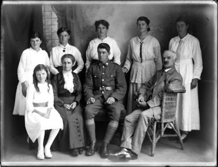 Glass plate negative of the Tylee family from Kahui Road, Rahotu. Standing in the back row from left is Mira (later Ashley), Sylvia (later Kitchingman), Eileen (later Dawson), Joyce (later Larking) and Stephanie (later Honeyfield) Tylee. Seated in the front from from left is Ethel (later Bartholomew), Emily Frederica (nee Miller), Private Wilfred Arthur and George Richardson Tylee. George is seated in a wicker chair and a studio setting with a window and draped curtain can be seen in the background. Photograph (ref: PHO2015-0050 ) held by Puke Ariki Museum, New Plymouth, New Zealand : pukeariki.com - No known copyright restrictions.
