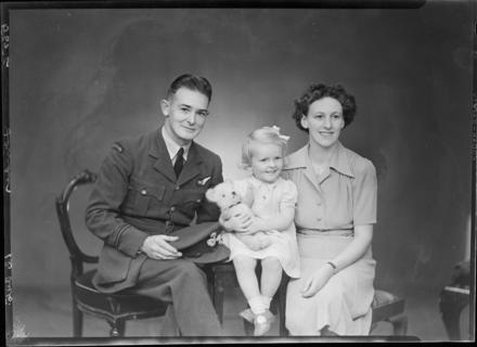 Serviceman Leslie Richard Lander seated with his young daughter and wife, Gwendoline Emily Lander. Leslie served in the Royal Air Force during World War Two (II). Photograph (ref: SW1944.2168) held by Puke Ariki Museum, New Plymouth, New Zealand : pukeariki.com - Please do not reproduce without permission from Puke Ariki. Contact images@pukeariki.com for more information.