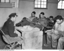 Photograph of 77 Squadron RAAF pilots examining maps and taking notes during a pre-flight briefing, taken March 1951 in Korea. Flight Lieutenant Max Scannell is seated third from left. Australian War Memorial, DUKJ3977. Image has no known copyright restrictions.