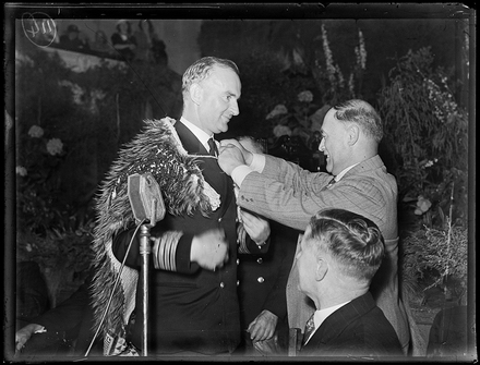 Captain Parry of HMS Achilles. Showing Captain Parry of HMS Achilles being presented with a Maori cloak at a reception at the Auckland Town Hall. February 1940. Auckland Libraries Heritage Collections 1370-289-6. Copyright or other restrictions may apply to this image.