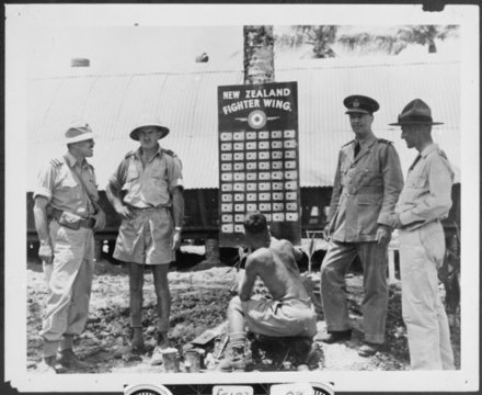 Group around the New Zealand Fighter Wing score board, Odonga (New Georgia), Solomon Islands. Ref: 1/2-106437-F. Alexander Turnbull Library, Wellington, New Zealand. /records/23097642